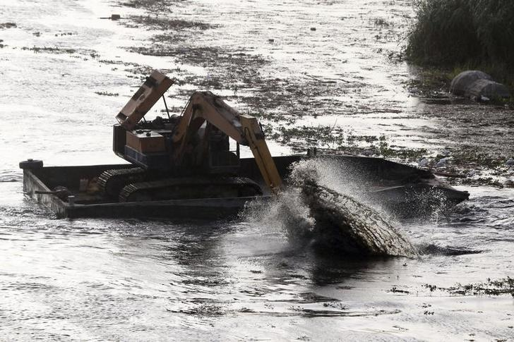 An excavator dredges the River Nile as part of a clean up operation in Cairo