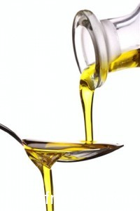 extra virgin olive oil being poured onto a spoon